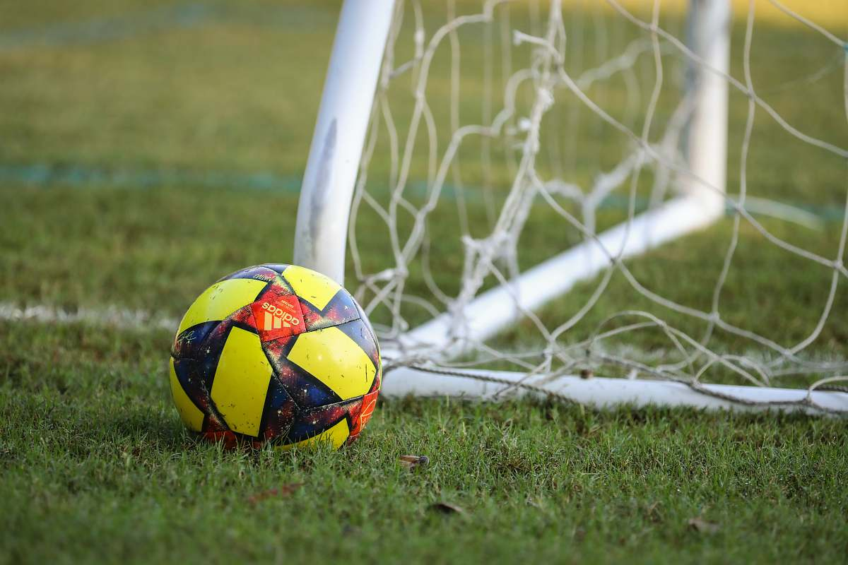 soccer red blue and yellow soccer ball on green grass field futbol